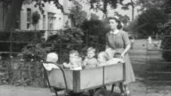 1950 TS Nanny pushing cart carrying toddlers through the gate, rounding the corner, and down the lane at group home facility / United Kingdom