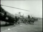 Narrated / 1949 Newsreel / A group of Marines run toward a helicopter / Marines board the helicopter and strap themselves in / The propeller starts...