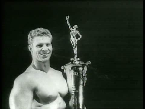 Narrated / 1949 Newsreel / Muscular men in bathing suits circle around the stage and flex for the crowd / Crowd applaud contestants /Man poses and...