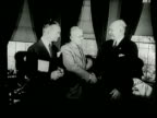 Narrated / President Truman Shakes hands with incoming Secretary of Defense Louis Johnson then crosses the other hand across his body and shakes...