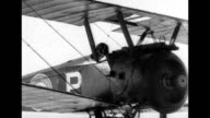 Narrator explains how airplanes were used for observation during WWI / plane flying in the sky / countryside smoking from gun fire / machine mounted...