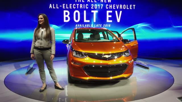 WS narrator introduces Bolt EV revolving on turntable / WS Bolt revolving on turntable / CU dashboard PAN LEFT inner door panel / WS rear cargo area...