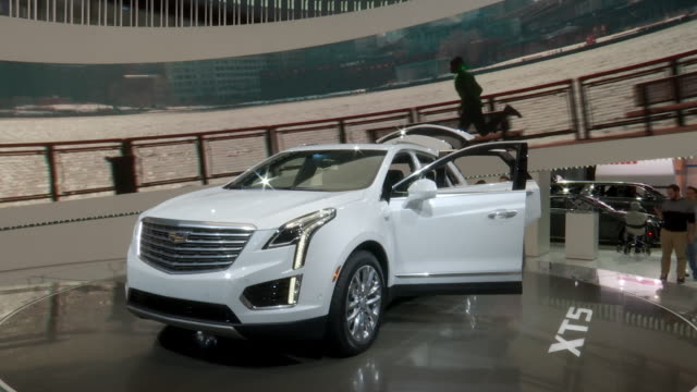 WS narrator introduces XT5 revolving on turntable / WS Cadillac on turntable / CU rear seats / MS rear wheel / CU mirror / MS dashboard PAN LEFT to...