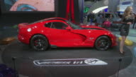 WS narrator talks about car as Viper revolves on turntable / CU Viper hood emblem / WS front quarter view and driver side profile as car revolves on...