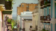 Narrow street w/ cars parked curbside people walking TU buildings