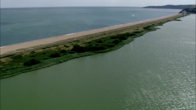 A narrow strip of sand bisects bodies of water on the southwest coast of England. Available in HD.