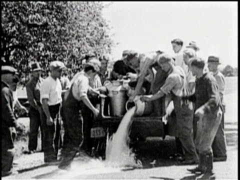 Nation backs NRA drive to end strikes/ A group of men stand in the road to stop a milk truck / They pour the barrels of milk out onto the road / Men...