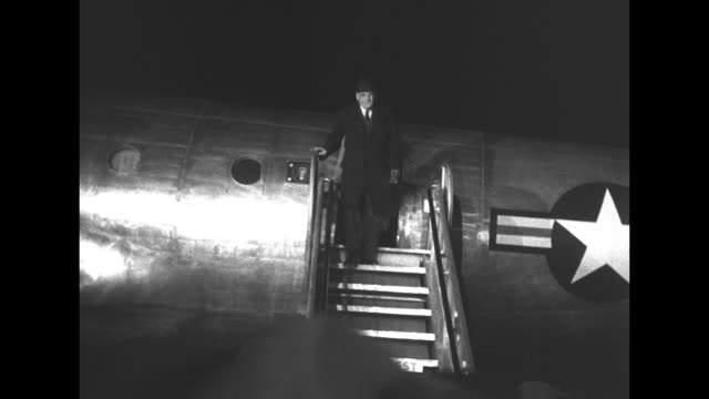 US Army plane on tarmac at Haneda Airport throng of reporters as steps pushed up to door / US Special Envoy John Foster Dulles down steps greeted by...