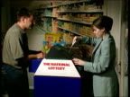 Possible 40 million pound jackpot R29079410 ENGLAND London INT Customer handing over National Lottery slip to woman who feeds it into lottery machine...
