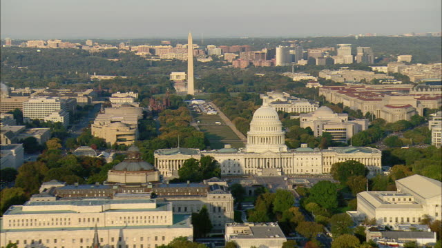 LOW AERIAL National Mall, Library of Congress and U.S. Capitol and U.S. Supreme Court buildings, Washington Monument in background, Washington D.C., USA