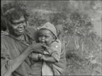 Native aborigine family in bush cooking over a fire / woman nurses young baby two men and one woman seated on ground with body paint use axe and...