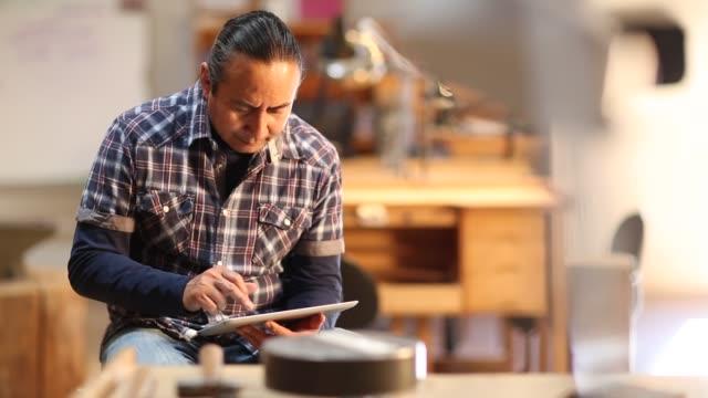 Native American artist using digital tablet in his art studio
