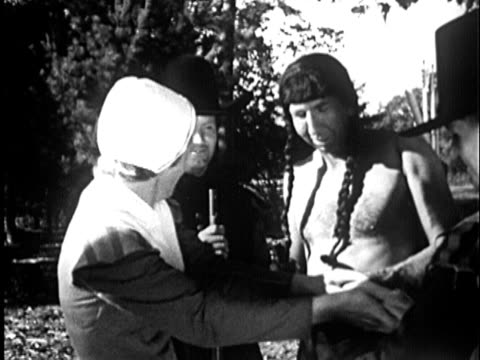 1955 B/W REENACTMENT MS Native American man with Pilgrim man and woman; CU hand pouring corn seeds from puch into mans hand / New England, United States / AUDIO