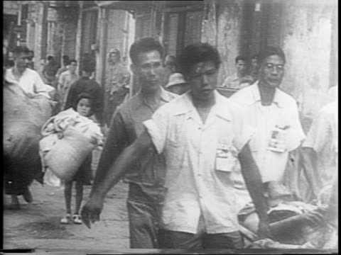 Native Filipinos fight fires in Manila with water hoses / scenes of destroyed buildings / young teen throws water on smoky wood / civilians carry and...