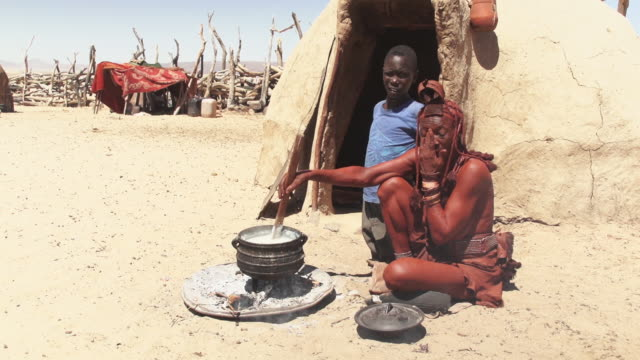 MS Native himba woman stirring pot with boy in front of clay hut / Himba, Kunene, Namibia