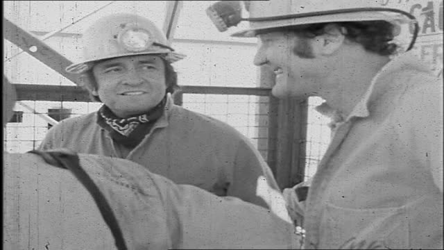 Natural Sound various shots Johnny Cash in overalls and wearing miners lamp hard hat getting into Mount Charlotte Gold mine shaft lift and descending...