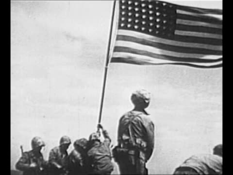 US Navy Corpsman John Bradley and US Marines Ira Hayes Michael Strank Rene Gagnon Harlon Block and Franklin Sousley raise US flag atop Mount...