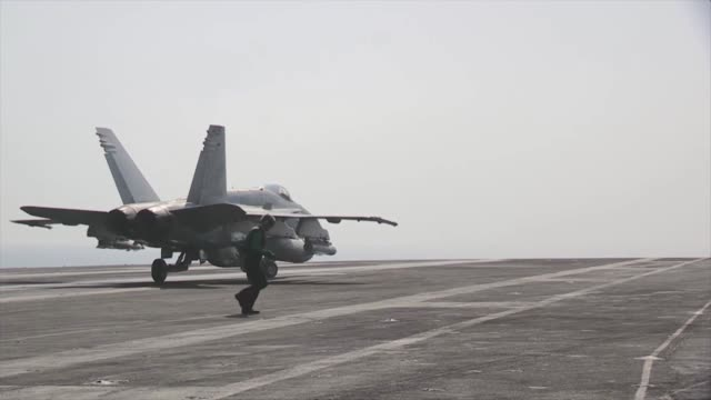 US Navy F/A18F Super Hornets return to the flight deck aboard the aircraft carrier USS George HW Bush following a mission over Iraq Then F/A18F Super...