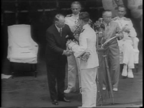 Navy Graduates fill into a packed auditorium / the men stand in rows / a man in uniform delivers a large bundle of diplomas to a man in a suit who in...