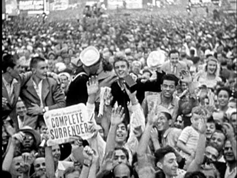 1945 B/W LS Navy man kissing woman in huge crowd in street cheering for end of WWII / United States / AUDIO
