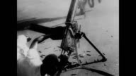 / Navy men loading guns and running on ship as bomber plane passes overhead / African American soldier lying on deck with a machine gun firing into...