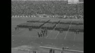 WS Navy midshipmen from the US Naval Academy lined up in formation on field at Baltimore's Municipal Stadium with packed stands in the background...