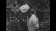 US Navy officer shaking hands with men in a line / MS young man and older woman kissing street and buildings in bg / MS young black sailor and older...