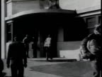 Navy pilots in flight uniform walking in to out of Administration building of Naval Aircraft Factory Workers backing aircraft out of hangar HA WS...