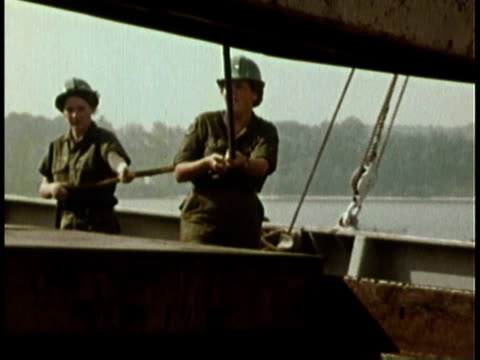 1979 MONTAGE Navy women operating winches and loading equipment aboard ship / United States