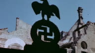 LA Nazi eagle and swastika against the sky and bomb damaged buildings / Munich Germany