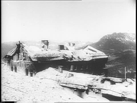 Nazi emblem / Berchtesgaden / wrecked building / US soldier standing guard silhouetted in doorway / interior of wrecked room with soldier standing...