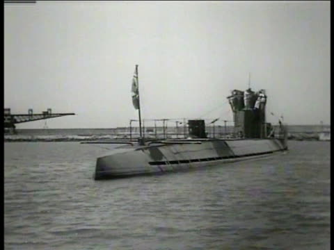 NAZI UBOAT WS Nazi flag w/ swastika WS Nazi UBoat submarine docked in harbor MS German Nazi sailor on upper deck w/ 25 on hull WS Sailor giving out...