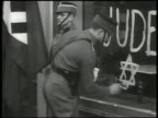 DRAMATIZATION Nazi soldiers rousting office workers Nazi soldier painting Star of David below 'Juden' on shop window Nazi soldiers fighting owners in...