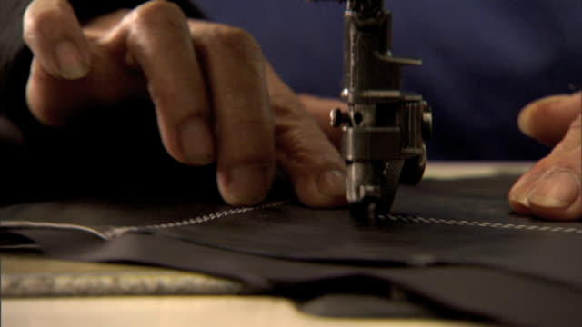 MCU Needle plate of sewing machine w/ unidentifiable hands sewing thread lace through cowhide gloves Sports