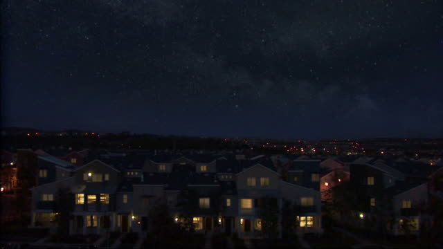 Neighborhood at night with shooting star.