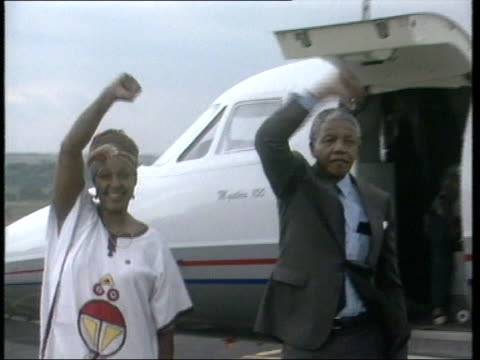 Nelson Mandela and wife Winnie make triumphant gesture on runway after arriving in Johannesberg