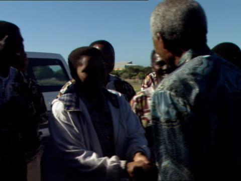 Nelson Mandela greeting youth choir with US first lady Hillary Clinton Nelson Mandela visits his old prison cell on Robben Island Nelson Mandela was...