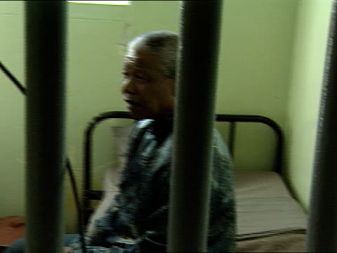 Nelson Mandela sitting in his cell Nelson Mandela visits his old prison cell on Robben Island Nelson Mandela was imprisoned on Robben Island for18...