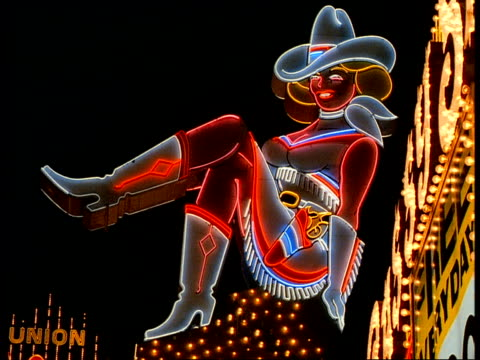 A neon cowgirl sign glows above the Glitter Gulch strip club on Fremont Street in downtown Las Vegas.