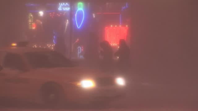 Neon lights visible though blizzard as pedestrians struggle on sidewalk Manhattan Available in HD