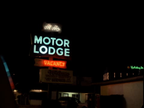 WS, Neon motel sign illuminated at night, buildings in background, Reno, Nevada, USA