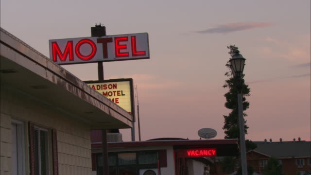 Neon vacancy and motel signs are lit against a sunset sky.