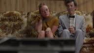 MS TU Nerdy couple sitting on sofa side by side / Orem, Utah, USA
