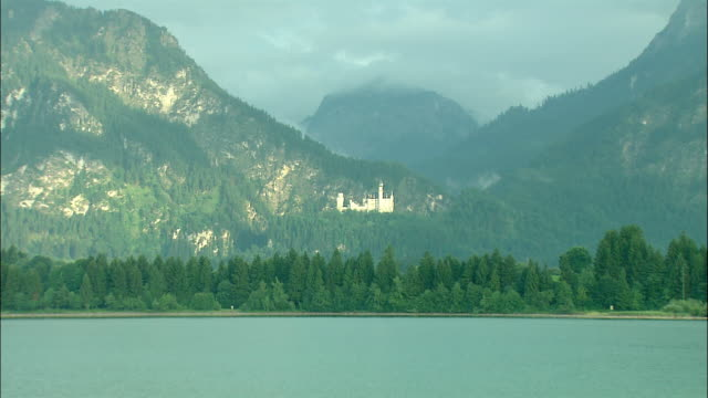 WS ZI Neuschwanstein Castle in mountain landscape, Lake Starnberg in foreground, Bavaria, Germany
