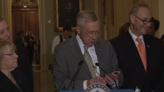 Nevada Senator Harry Reid answers reporter question about a possible global economic downturn by looking at his phone for the current market figure...