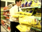 New bans LIB Worker in Asda supermarket placing crisps onto shelf CS Ingredients listed on bag of crisps including genetically modified soya and maize