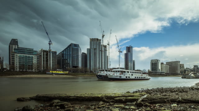 New business and residential developments under construction on the south embankment of the Thames river heavy storm clouds pass over head and clear to blue skies