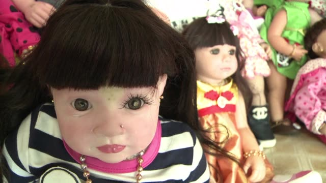 A new craze has emerged in Thailand for pampering lifelike dolls in order to bring good fortune