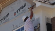 New home construction a painter paints the eave of a new townhouse