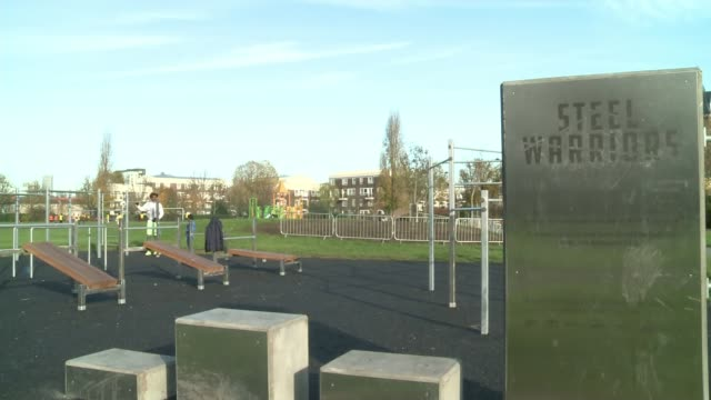 New outdoor gym partly made from seized and surrendered knives ENGLAND London Poplar Langdon Park EXT Man and child on outdoor gym bars 'Steel...